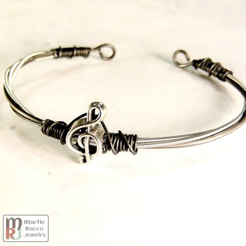Guitar,String,open,bangle,with,pewter,treble,bead,on,black,annealed,steel,wire.,Guitar String open bangle with pewter treble clef bead on black annealed steel wire.