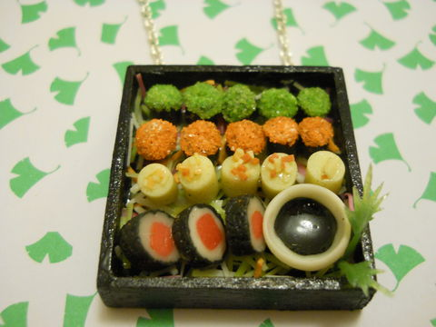 Sushi,Bento,Box,Necklace,3,Kitsch wooden Bento Box pendant filled with miniature kawaii sushi, wasabi roe and maki on a silver necklace.  pendant filled with silver glitter  and backed with silver glitter. The pendant also features a dog with cherries and a cake  silver gold neckla