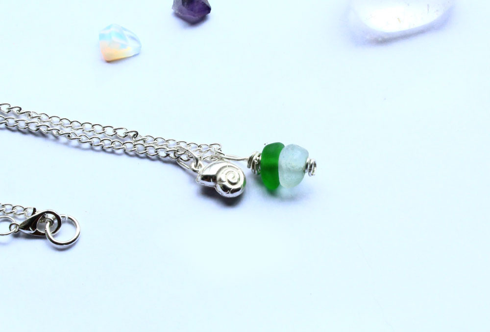 Green sea glass and silver necklace with ammonoid charm