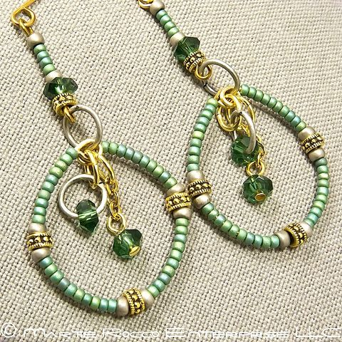Long,green,round,hoop,earrings,in,seed,beads,and,crystals.
